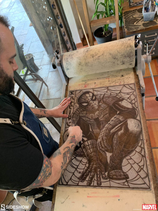 Peter Santa-Maria works to carve the Spider-Man Linocut