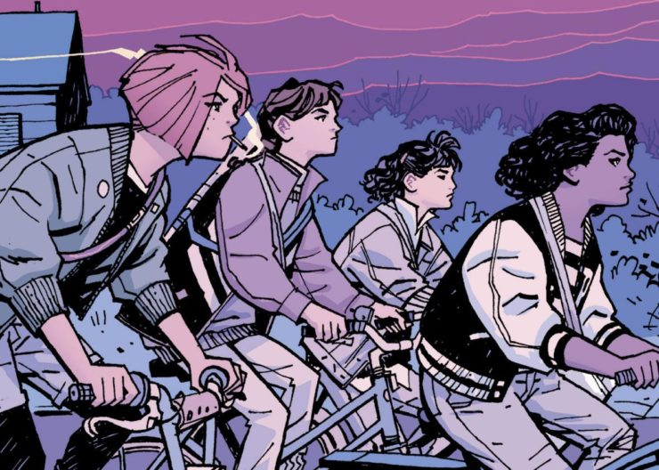 The Paper Girls riding on their bikes