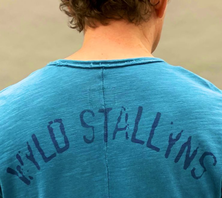 Alex Winter as Bill wearing a shirt that says Wyld Stallyns on the back