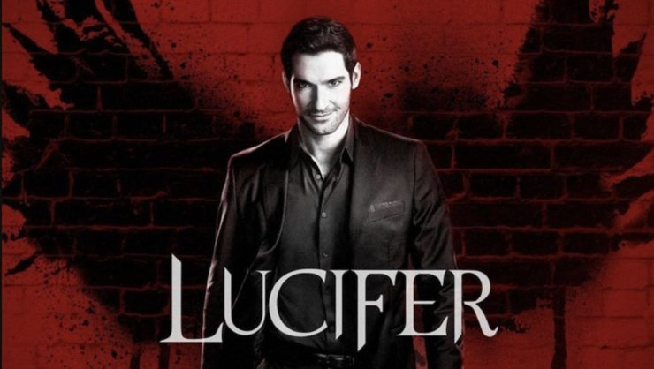 Lucifer in black and white with a red brick wall behind him and black wings spray-painted on the wall