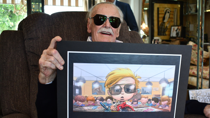 A Picture of Stan Lee holding a drawing of a young version of himself