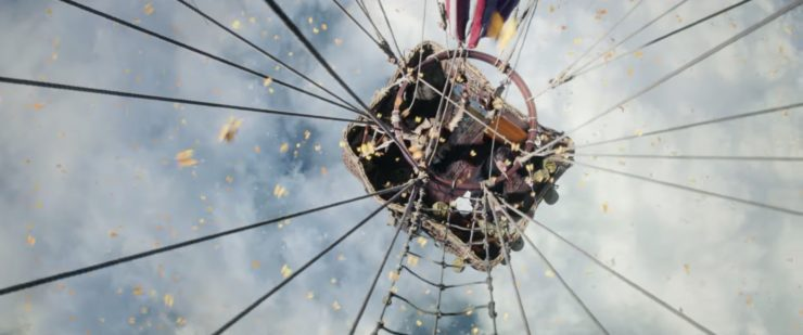 the main characters of The Aeronauts in a hot air balloon as yellow butterflies fly all around them