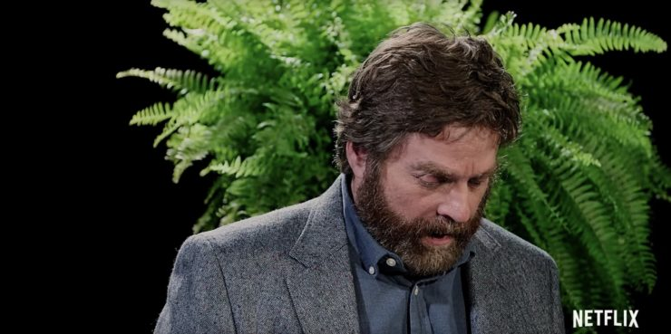 Zach Galifianakis looking down at his notes in front of a fern