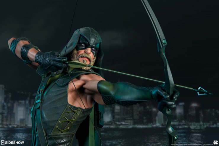 Green Arrow drawing his bow down across a city