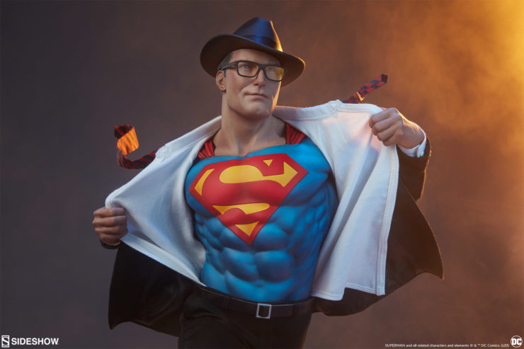 Half body view of Superman, as he pulls of his shirt and suit coat, with his hat and glasses still on, tie flying off in the wind, revealing his Super S