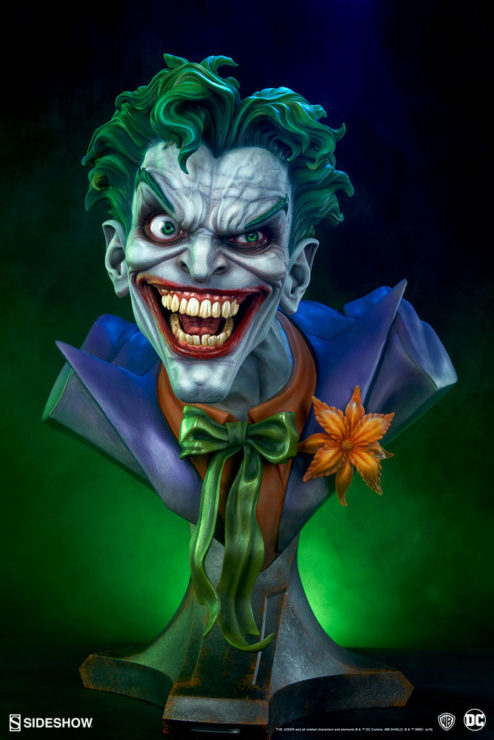 Full front view of The Joker Life-Size Bust with green lights behind it