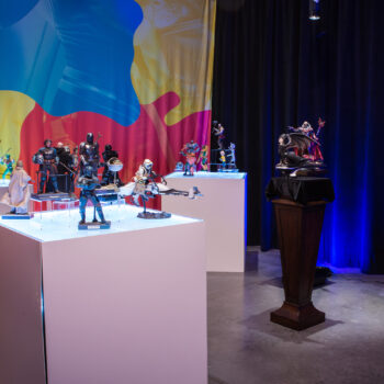 (from left to right) MicroCon Display with Power Rangers, Mandalorian, and Masters of the Universe Collectibles