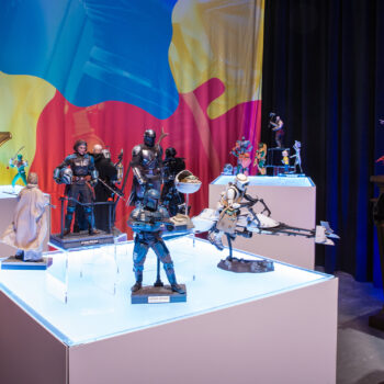 (from left to right) MicroCon Display with Power Rangers, Mandalorian, and Masters of the Universe Collectibles and Elvira Statue