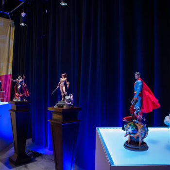 MicroCon Display with DC Comics Collectibles on right and Masters of the Universe Collectibles on left, with Elvira Statue