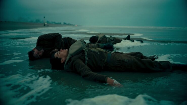 Tommy (Fionn Whitehead) a French Soldier (Damien Bonnard) sleep on the beach and in the surf in Christopher Nolan's Dunkirk (2017)