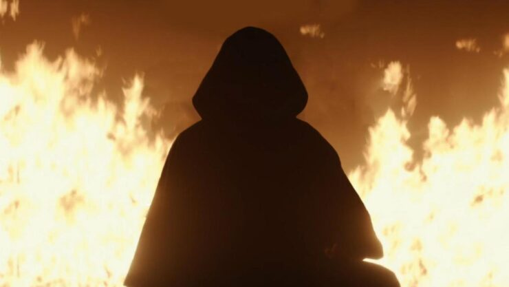 Cloaked villain in front of fire