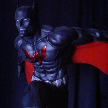 Batman Beyond in front of a black curtain