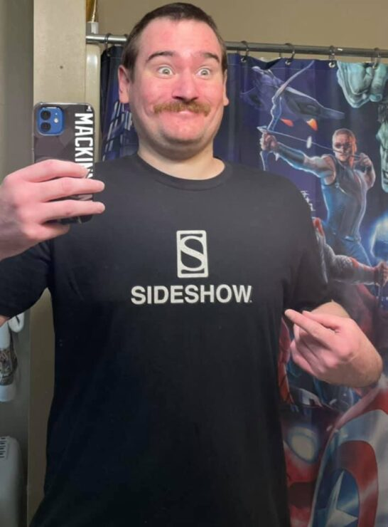 Let Your Geek Sideshow Facebook Group member Ian C. smiles as he wears a black Sideshow branded t-shirt