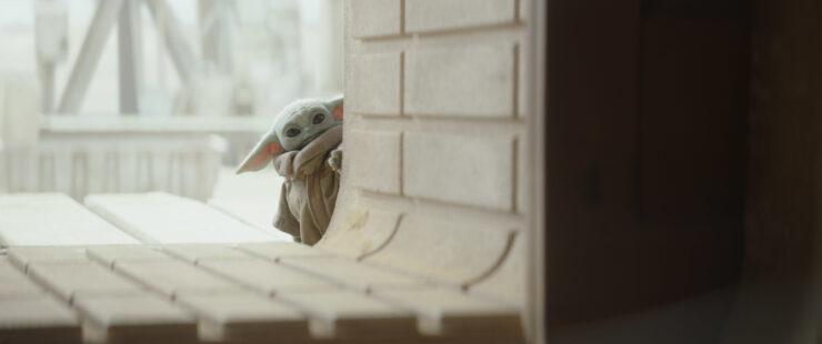 Grogu peeks around the corner in a still from The Mandalorian