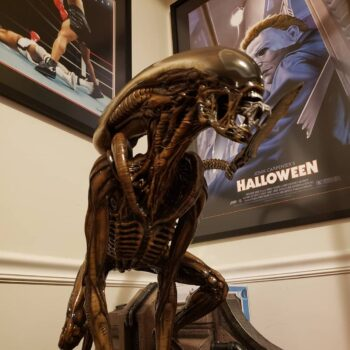 xenomorph collectible with posters in background