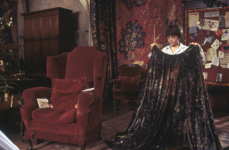 Harry Potter, wearing glasses and striped pajamas, holds up the brown and black invisibility cloak while surrounded by the scarlet decor of the Gryffindor Common Room