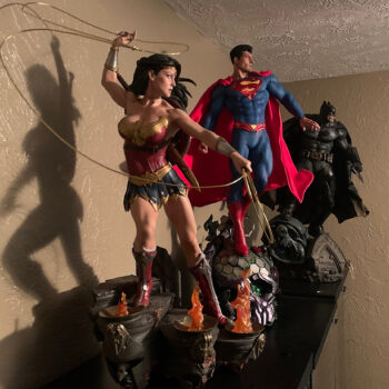 Wonder Woman Superman and Batman collectibles lined up and lit from the right