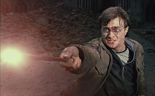 Bruised and bloody, Harry Potter uses a glowing wand to defend himself from a magical attack