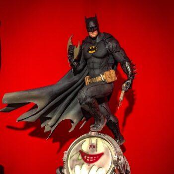 Batman perched atop Bat signal